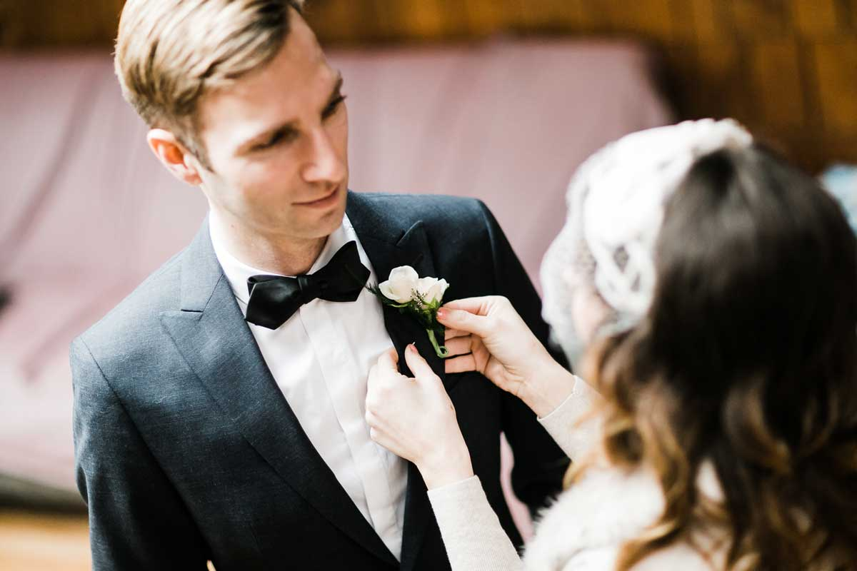 Amber fixes Chris's clothing before their Canlis wedding in Seattle.