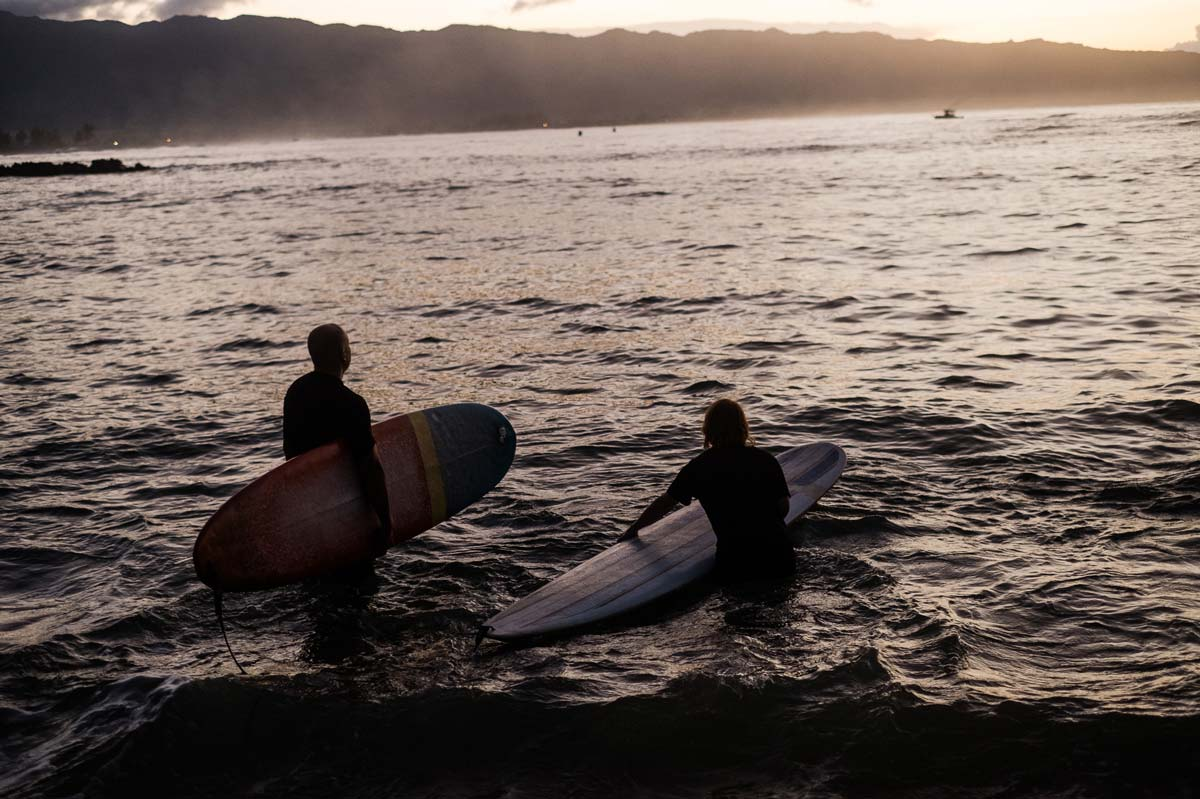 Kirk Mastin and Kathryn Stevens surfing at sunset in Honalulu.