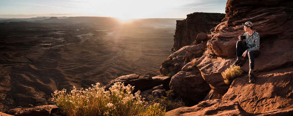Lucas Mobley about a cliff in Canyon Lands National Park at Sunset.