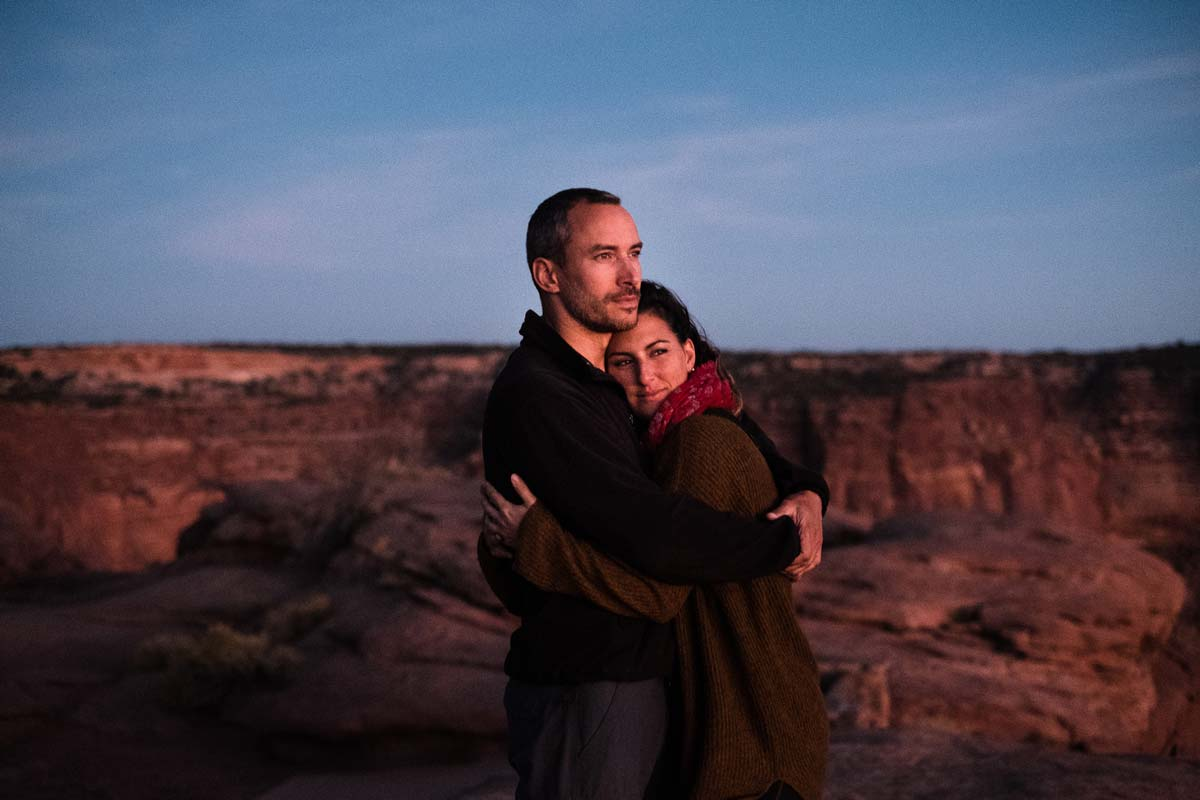 A couple embraces at sunset about Canyon Lands National Park